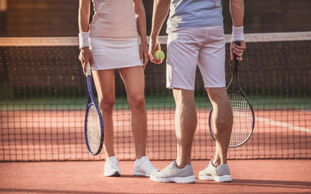 Cropped image of man and woman standing near on tennis court outdoors