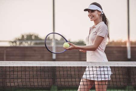 아름 다운 젊은 여자 테니스 코트 야외에서 테니스 재생하는 동안 웃
