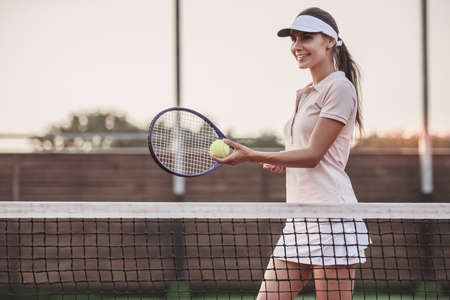 Beautiful young woman is smiling while playing tennis on tennis court outdoors
