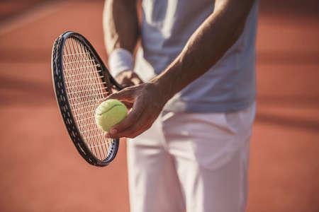 Imagen recortada de hombre guapo jugando al tenis en la cancha de tenis al aire libre Foto de archivo - 88859488