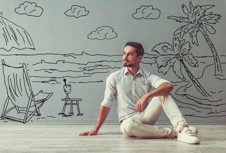 De knappe mens in slimme vrijetijdskleding kijkt weg, droomt en glimlacht terwijl het zitten op de vloer naast de muur met getrokken kust