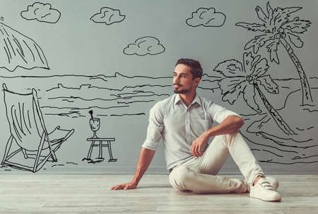 Handsome man in smart casual clothes is looking away, dreaming and smiling while sitting on the floor next to the wall with drawn seaside