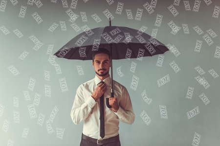 Handsome businessman in classic suit with umbrella is looking at camera, drawn banknotes are falling like rain, on gray background