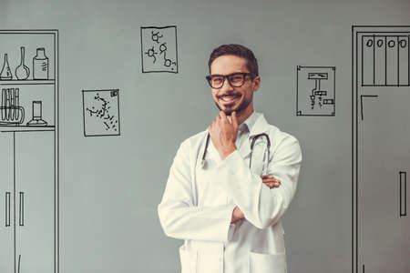 Handsome doctor in medical coat and eyeglasses is looking at camera and smiling, on gray background with drawn office furniture
