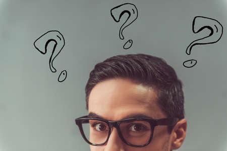 L'immagine potata del fronte dell'uomo bello in occhiali e con i punti interrogativi lassù sta esaminando la macchina fotografica, su fondo grigio Archivio Fotografico - 89127287
