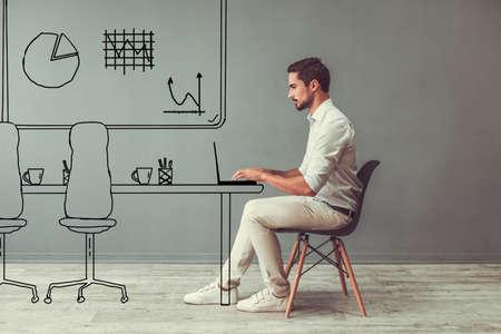 灰色の背景に描かれた事務所で椅子に座りながらノート パソコンを扱うスマート カジュアルな服でハンサムな男 写真素材 - 89127289