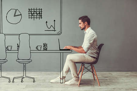 Handsome man in smart casual clothes is working with laptop while sitting on the chair on gray background with drawn office