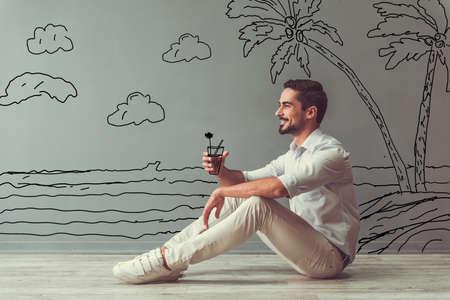 De knappe mens in slimme vrijetijdskleding imiteert het houden van een cocktail en glimlacht terwijl het zitten op de vloer naast de muur met getrokken kust