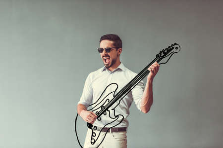 Handsome young man in smart casual clothes and sun glasses is imitating playing guitar and singing, on gray background Banco de Imagens