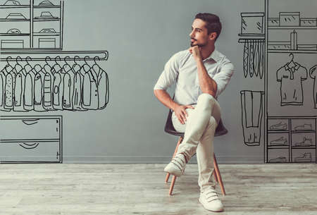 Handsome man in smart casual clothes is looking away and thinking while sitting on the chair on gray background with drawn mens store Stock Photo