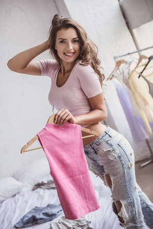 Beautiful girl in jeans is holding a new blouse, looking at camera and smiling while resting in her room at home