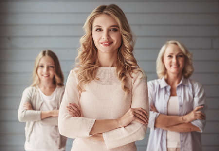 Beautiful women generation: granny, mom and daughter are looking at camera and smiling while standing with crossed arms, mom in the foreground Stock Photo