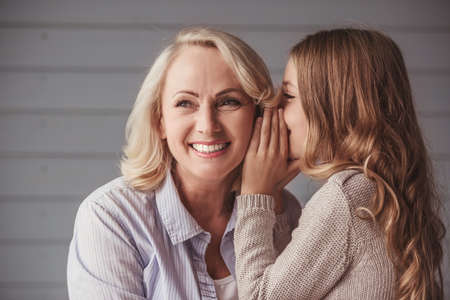 Beautiful granny is smiling while teenage granddaughter is whispering her something