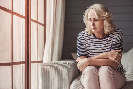 Beautiful sad senior woman is looking downward while sitting on couch at home Foto de archivo