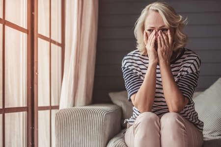 美しい悲しい年配の女性が泣いて、家でソファーに座っている間に涙を拭いている