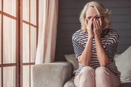 Beautiful sad senior woman is crying and wiping her tears while sitting on couch at home