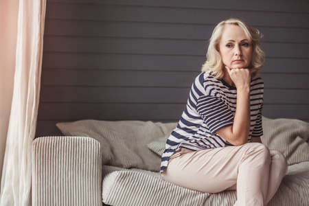 Beautiful sad senior woman is leaning on her hand and looking away while sitting on couch at home