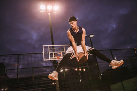 Stylish young basketball player in cap is jumping while playing basketball outdoors in the evening