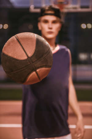 Stylish young basketball player in cap is holding a ball while standing on basketball court outdoors in the evening Stock Photo