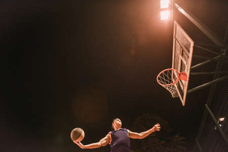 Stylish young basketball player in cap is jumping and shooting a ball through the hoop while playing outdoors at night