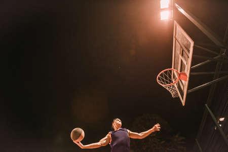 Légant jeune basketteur au bonnet saute et tire une balle à travers le cerceau en jouant dehors la nuit Banque d'images - 89602170