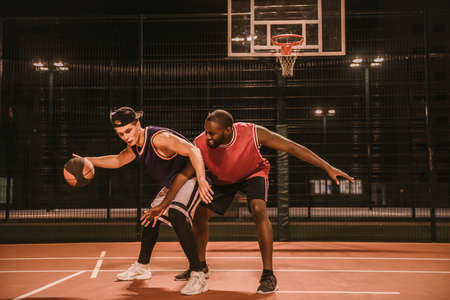 잘 생긴 남자 야간 야외 농구를 놀고있다. 스톡 콘텐츠 - 89602176