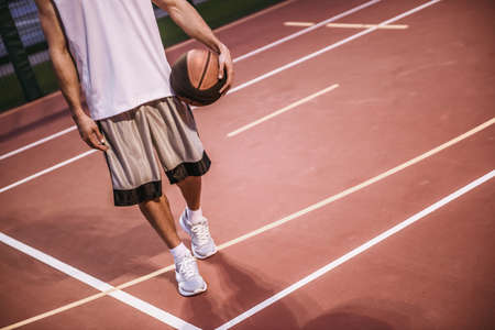 Cropped image of handsome basketball player standing with a ball on basketball court outdoors