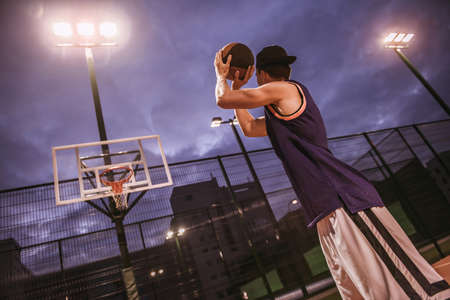 Stylish young basketball player in cap is shooting a ball through a hoop while playing on basketball court outdoors in the evening