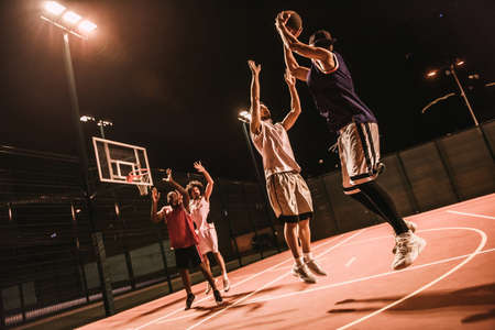 Handsome guys are playing basketball outdoors at night