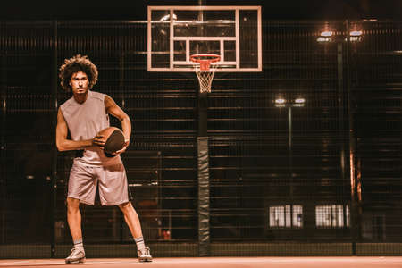 Attractive mulatto basketball player is playing basketball outdoors in the evening