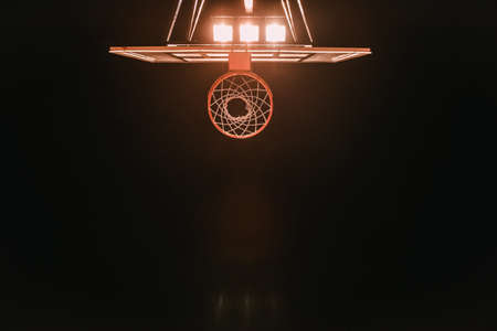 Bottom view of basketball hoop on night sky background, lights are turned on