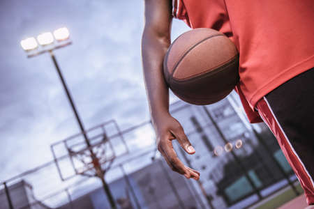 Cropped image of Afro American basketball player standing with a ball on basketball court outdoors Stock Photo