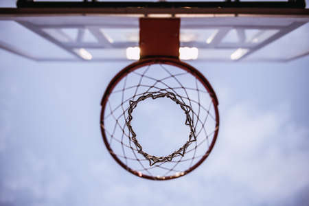 Bottom view of basketball hoop on evening sky background