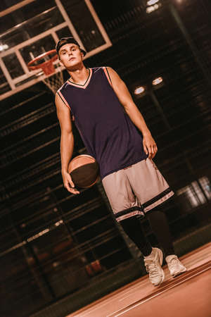 Full length portrait of stylish young basketball player in cap standing with a ball on basketball court outdoors at night