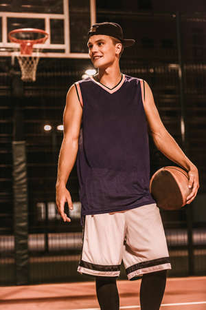 Stylish young basketball player in cap is standing with a ball on basketball court outdoors at night