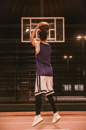 Full length portrait of stylish young basketball player in cap shooting a ball through the hoop while playing outdoors at night