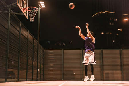 Full length portrait of stylish young basketball player in cap jumping and shooting a ball through the hoop while playing outdoors at night Zdjęcie Seryjne - 90372533