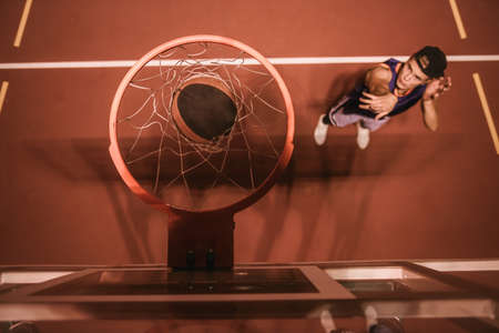 Top view of stylish young basketball player in cap shooting a ball through the hoop while playing outdoors at night