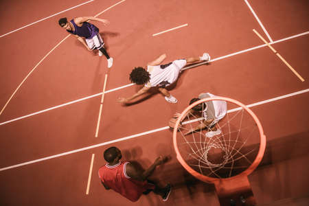 High angle view of handsome guys playing basketball outdoors at night