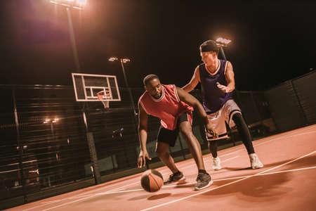 ハンサムな男は夜に屋外でバスケットボールをしています