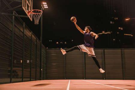 Full length portrait of stylish young basketball player in cap jumping and shooting a ball through the hoop while playing outdoors at night
