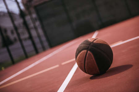 Dark-colored basketball lying on basketball court outside