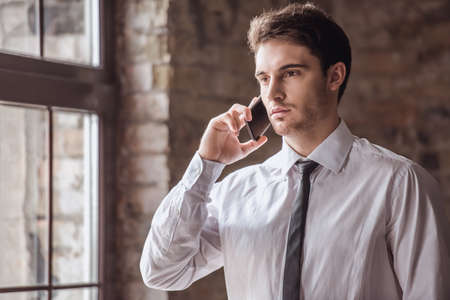 Handsome pensive young businessman in suit is talking on the mobile phone while standing indoors