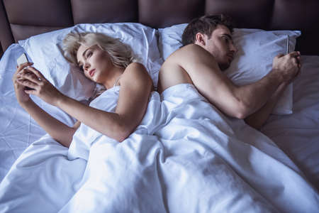 Beautiful young woman and man are using their smart phones while lying back to back in bed at home Stock Photo