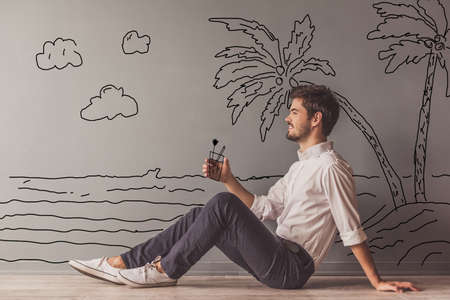 Handsome young man in smart casual clothes is imitating holding a cocktail and smiling while sitting on the floor next to the wall with drawn seaside