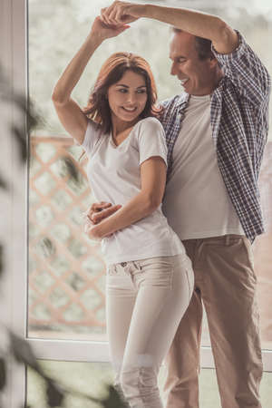Beautiful happy couple is dancing and smiling while resting at home