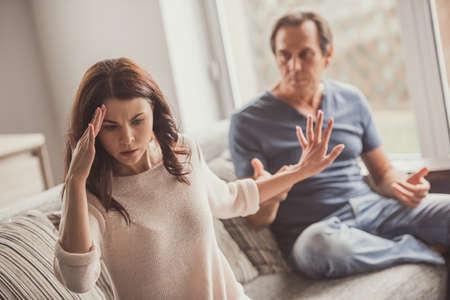 집에서 소파에 앉아있는 동안 성인 부부가 다투고 있습니다. 스톡 콘텐츠