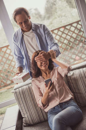 Couple at home. Handsome mature man is covering his beautiful wife eyes and giving her a present, both are smiling