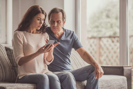 Couple of adults are using a smart phone and talking while sitting on couch at home Reklamní fotografie