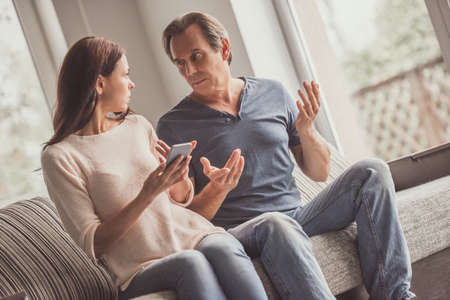 Couple of adults are using a smart phone and talking while sitting on couch at home Stock Photo